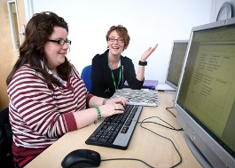 AmyCrossland.jpg, 2 women say at computers, smiling and talking